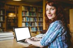 Mogen student som studerar i arkiv med bärbara datorn royaltyfria bilder
