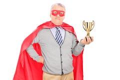 Mogen superhero som rymmer en trofé Royaltyfri Bild