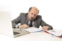 Mogen upptagen affärsman för pensionär med flinten på hans funktionsdugliga stressat för 60-tal och frustrerat på skrivbordet för Arkivbild