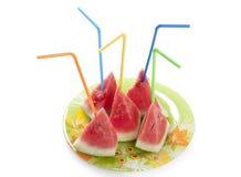 Mogen vattenmelon till stycken med en tubule på plattan Fotografering för Bildbyråer