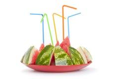 Mogen vattenmelon till stycken med en tubule på plattan Royaltyfri Bild