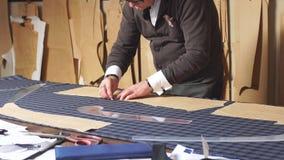 Mogen yrkesmässig skräddare som arbetar med måttstången som förbereder tyg för kläderframställning arkivfilmer