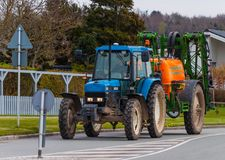 Blue tractor with a orange sprayer royalty free stock image