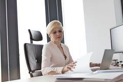 Moget affärskvinnaläsningdokument på skrivbordet i regeringsställning arkivfoton