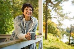 Moget attraktivt kvinnaanseende på terrass med koppen av varmt kaffe fotografering för bildbyråer