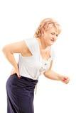 Moget blont kvinnligt lidande från ett tillbaka smärtar Fotografering för Bildbyråer
