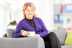 Moget damsammanträde på soffan och drickakaffe hemma Royaltyfri Bild
