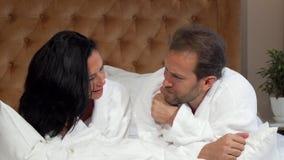 Moget gift par, i badrocksamtal som tillsammans ligger i säng på hotellet stock video