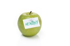 Moget grönt äpple och etikett med det sunda ordet, isolerat fotografering för bildbyråer