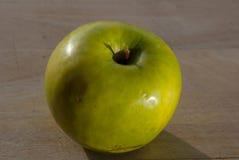Moget grönt äpple på träbrädet arkivbild