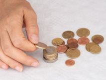 Moget kvinnahand som sätter mynt in i en hög, hög, på vit borddukbakgrund close Europeiska euromynt som räknar arkivbild