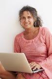 Moget kvinnasammanträde mot väggen genom att använda bärbara datorn Arkivbilder
