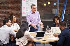 Moget möte för affärsmanStanding And Leading kontor av kollegor som sitter runt om tabellen fotografering för bildbyråer