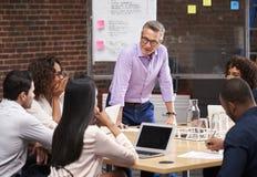 Moget m?te f?r aff?rsmanStanding And Leading kontor av kollegor som sitter runt om tabellen arkivfoton