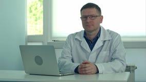 Moget manligt doktorssammanträde på skrivbordet med bärbara datorn och se kameran i hans klinikkontor stock video
