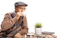 Moget mansammanträde på en kaffetabell och dricka från en kopp royaltyfri fotografi