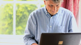 Moget mansammanträde vid ett fönster genom att använda hans dator stock video