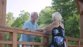 Moget paranseende på bron som rymmer händer som talar och ler Härlig hög kvinna i sommarklänning och arkivfilmer