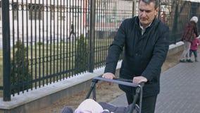 Moget skjuta för man behandla som ett barn sittvagnen Gå på en härlig vårdag Farfar och sondotter stock video