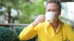 Moget stiligt mansammanträde och drickakaffe i coffee shop arkivfilmer