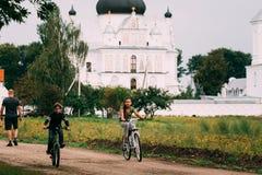 Mogilev, Bielorrusia El muchacho y un paseo de la muchacha monta en bicicleta cerca del St Nich fotos de archivo