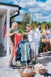 Moglie alla moda che porta il vestito rigonfio da estate che esamina nuovo vestito rosso la vendita di oggetti usati immagini stock libere da diritti