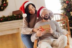 Moglie amorosa le che dà il regalo di Natale del marito Immagini Stock