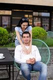 Moglie castana che abbraccia marito che si siede nella sedia al caffè della via fuori immagini stock