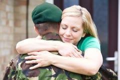 Moglie che abbraccia la casa del marito dell'esercito in permesso immagini stock libere da diritti