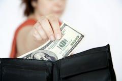 Moglie che cattura soldi dalla borsa Fotografia Stock