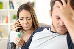 Moglie che chiama medico per aiutare il suo marito malato immagini stock libere da diritti