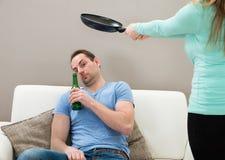 Moglie che colpisce marito con la pentola fotografie stock