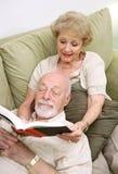 Moglie che legge al marito fotografia stock