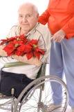 Moglie che spinge l'uomo di handicap in sedia a rotelle con flowe fotografia stock libera da diritti