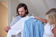 Moglie che veste marito immagini stock