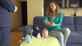 Moglie con il bambino sui soldi della presa del sofà dalla testa della famiglia del marito 4K video d archivio