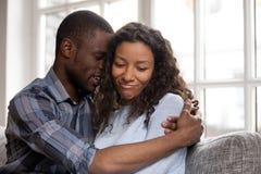 Moglie d'abbraccio di amore del marito afroamericano dopo il litigio immagini stock