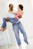 Moglie della holding del marito nel nuovo sorridere domestico Immagine Stock Libera da Diritti