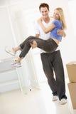 Moglie della holding del marito nel nuovo sorridere domestico Fotografie Stock Libere da Diritti