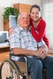 Moglie di amore accanto al marito in sedia a rotelle immagini stock libere da diritti