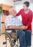 Moglie di amore accanto al suo marito in sedia a rotelle fotografia stock