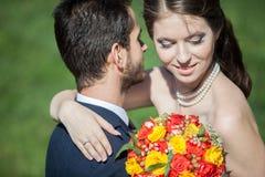 Moglie e sposo sul campo di erba nel giorno di estate soleggiato fotografia stock