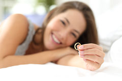 Moglie felice che guarda la sua fede nuziale fotografia stock