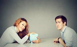 Moglie felice con il porcellino salvadanaio che si siede attraverso la tavola dal marito triste fotografie stock