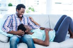 Moglie incinta che si rilassa sul rivestimento del marito immagine stock