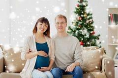 Moglie incinta con il marito a casa a natale fotografia stock