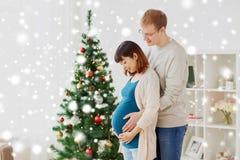 Moglie incinta con il marito a casa a natale fotografia stock libera da diritti
