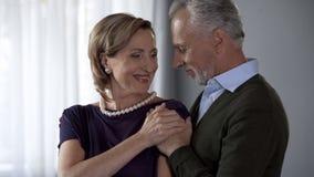 Moglie invecchiata felice della tenuta del marito dalle spalle da dietro, anniversario di nozze immagine stock