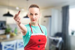 Moglie o domestica che mostra dito medio su fondo dell'interno fotografie stock libere da diritti