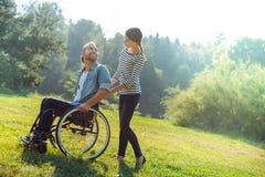 Moglie preoccupantesi che porta il suo marito disabile in una sedia a rotelle Immagine Stock